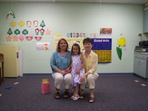 Amélie with her preschool teachers on the last day of school